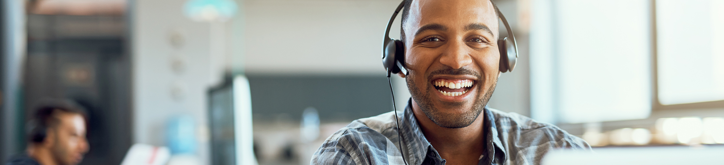 Man with headset smiling at camera in call center
