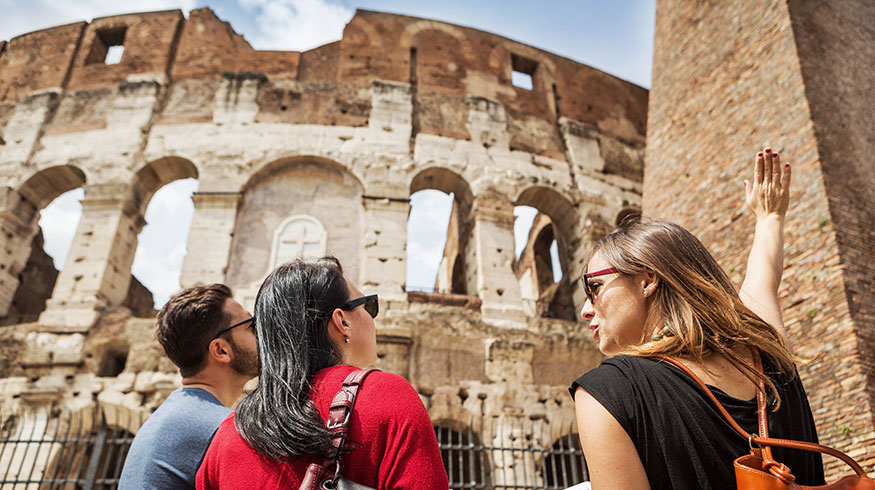 Female teacher points out details of some Roman ruins.