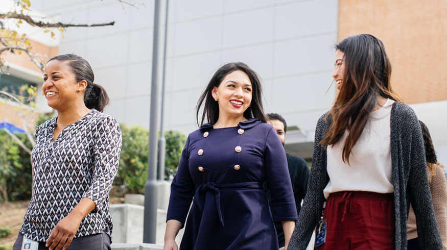 Three female students walk on campus with smiles on their faces.