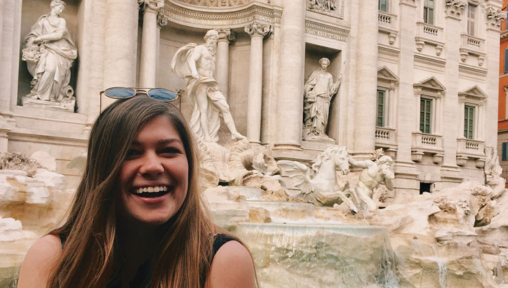 UCSB student Rachel smiles big in front of the famous Trevi Fountain with its aqua water and statues.