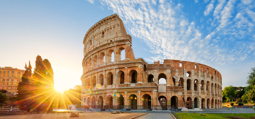 The sun rises behind the Colosseum on a beautiful day in Rome, Italy.