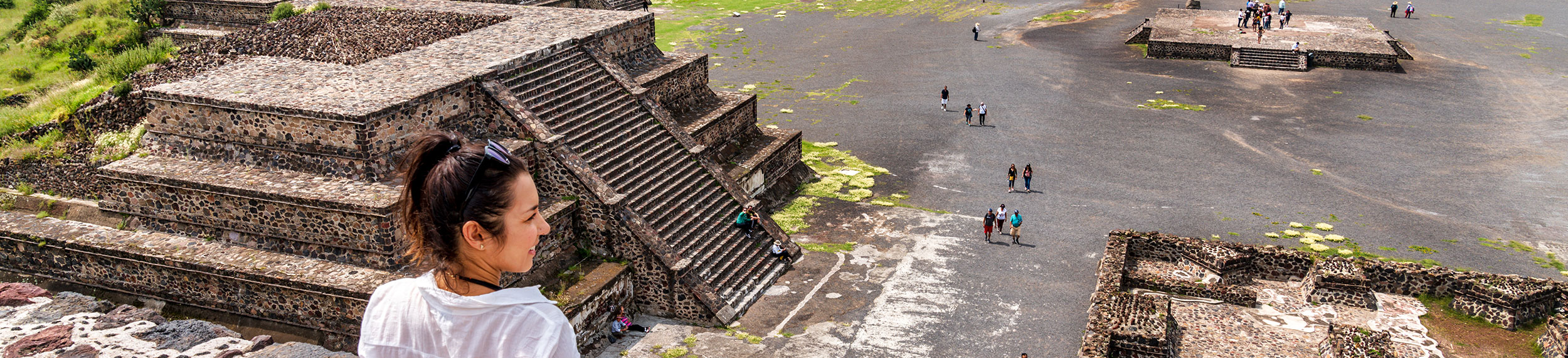 A young woman surveys the view around her from the top of one of the ancient Teotihuacan pyramids on a sunn day in Mexico City, Mexico.