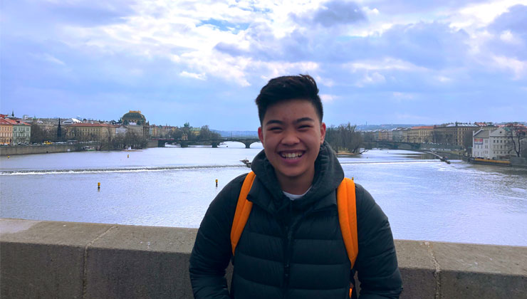 Leanne Nguyen-Phuoc of UC Irvine on a bridge smiling with a river behind him in Prague, Czech Republic.