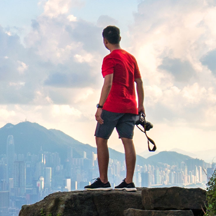 Man with camera looks at Hong Kong from on top of a hill on a cloudy day.