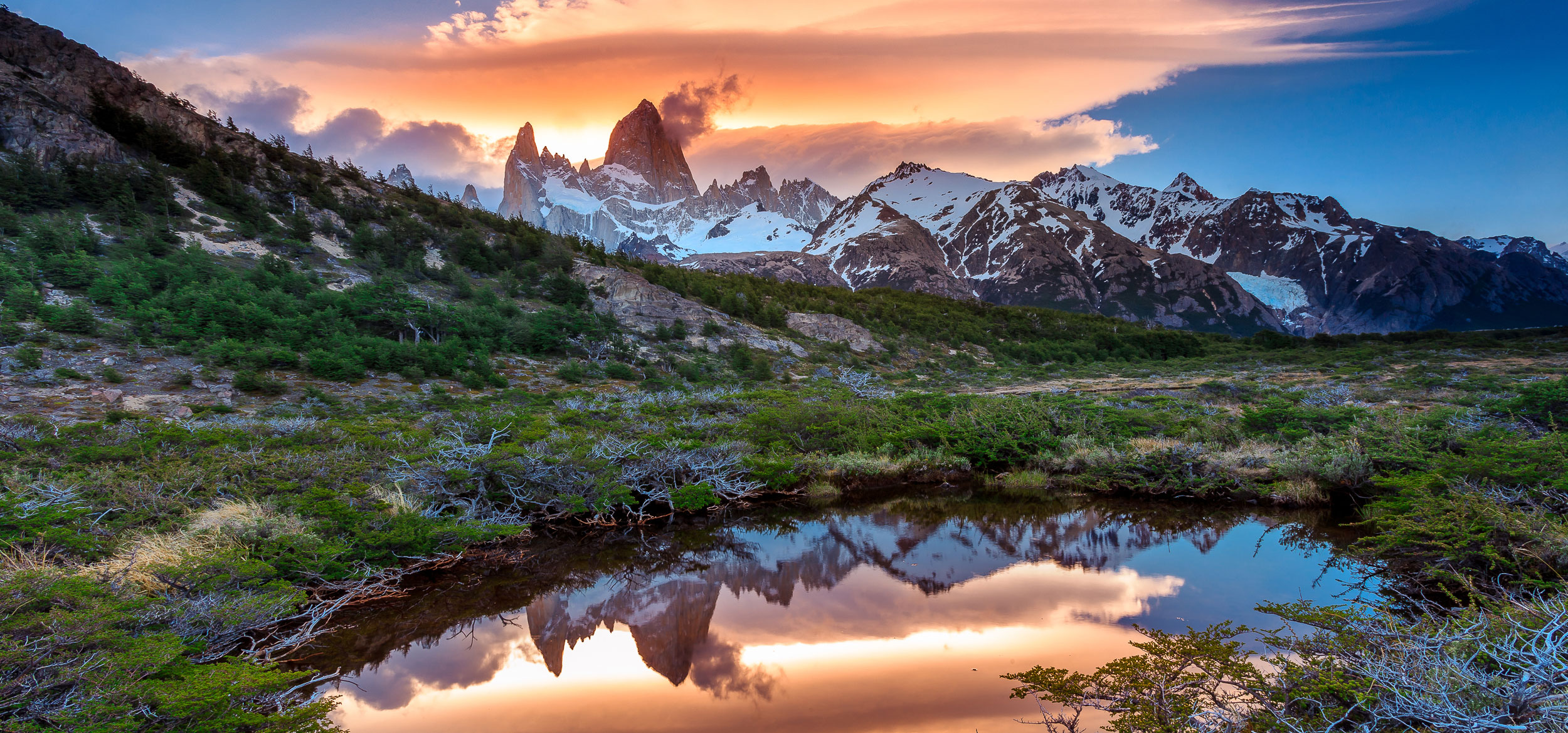 A sunset view of Mt Fitz Roy with a reflection in a grassy pond in Los Glaciares National Park, Argentina.