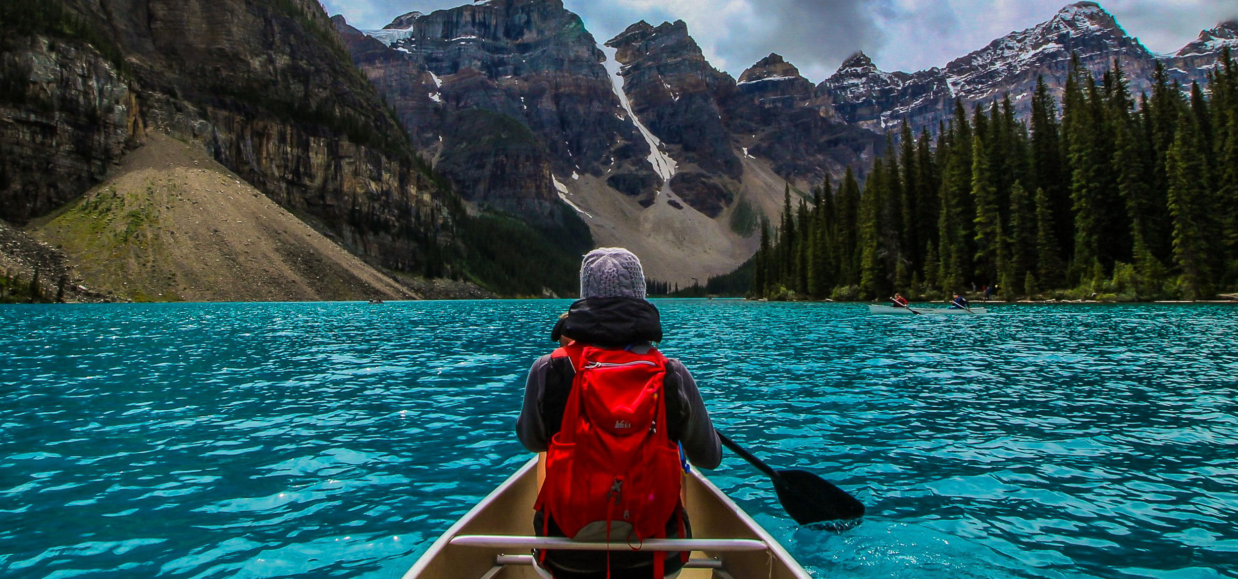 Woman canoeing on the turquoise water of Moraine Lake in Banff National Park, Canada.