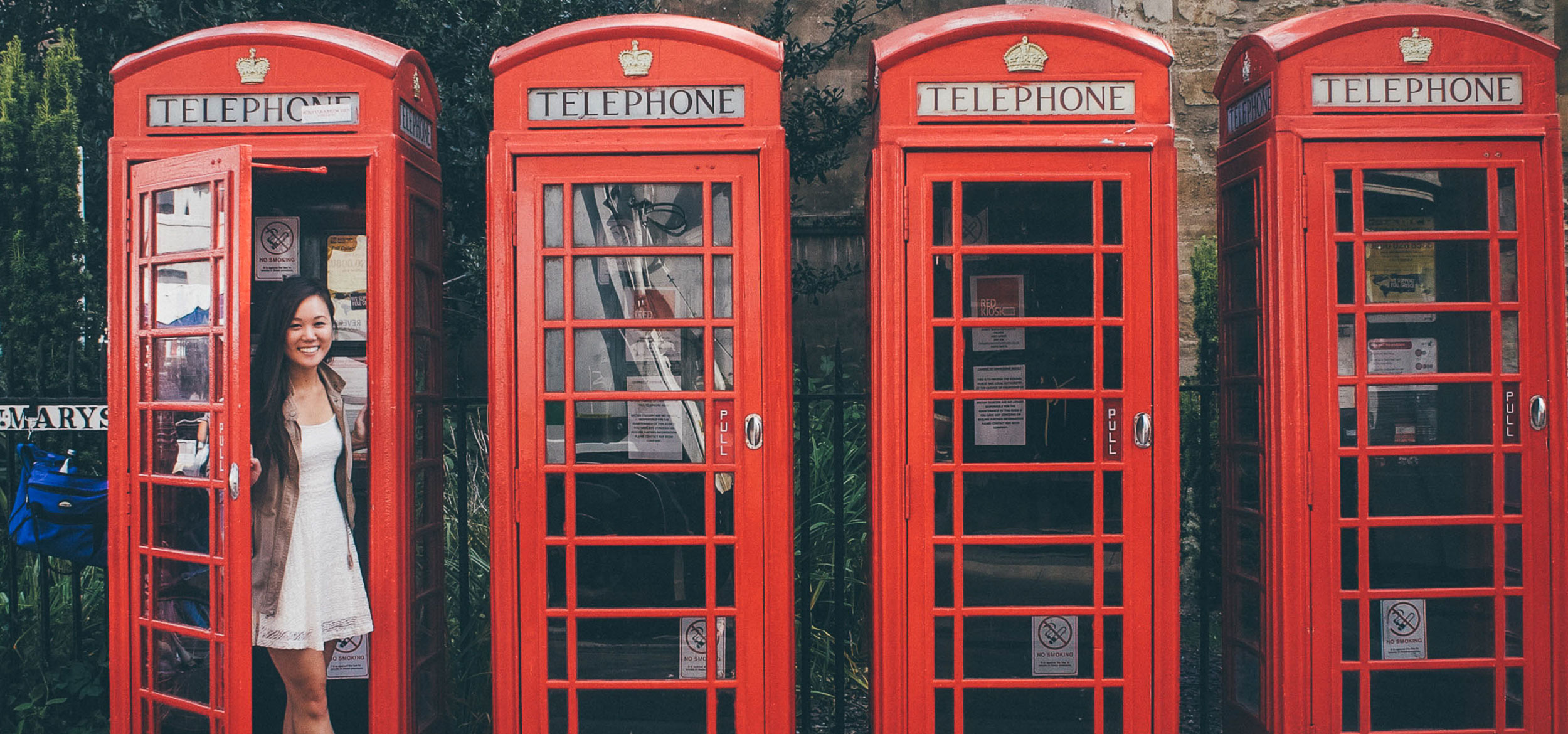 Student Jacqueline Woo from UC Berkeley stands next to four red telephone booths in London, UK-England.