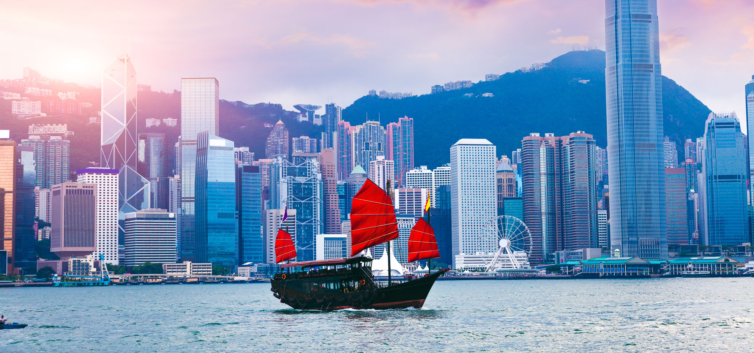 A junk boat with red, square sails crossing the Hong Kong Harbor in Hong Kong.