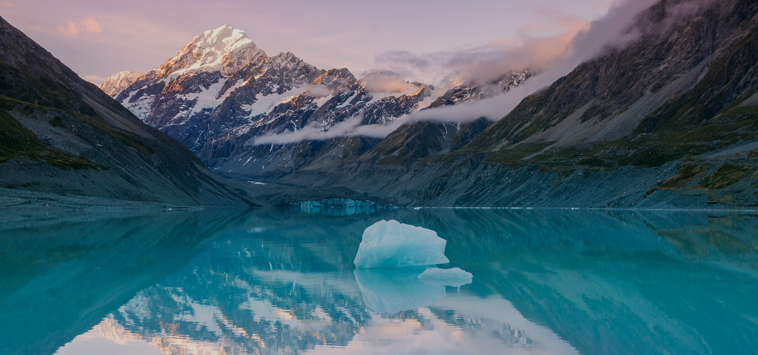 At sunset, the snowcapped peak of Mount Cook reflects in a still lake in a national park of New Zealand's South Island.