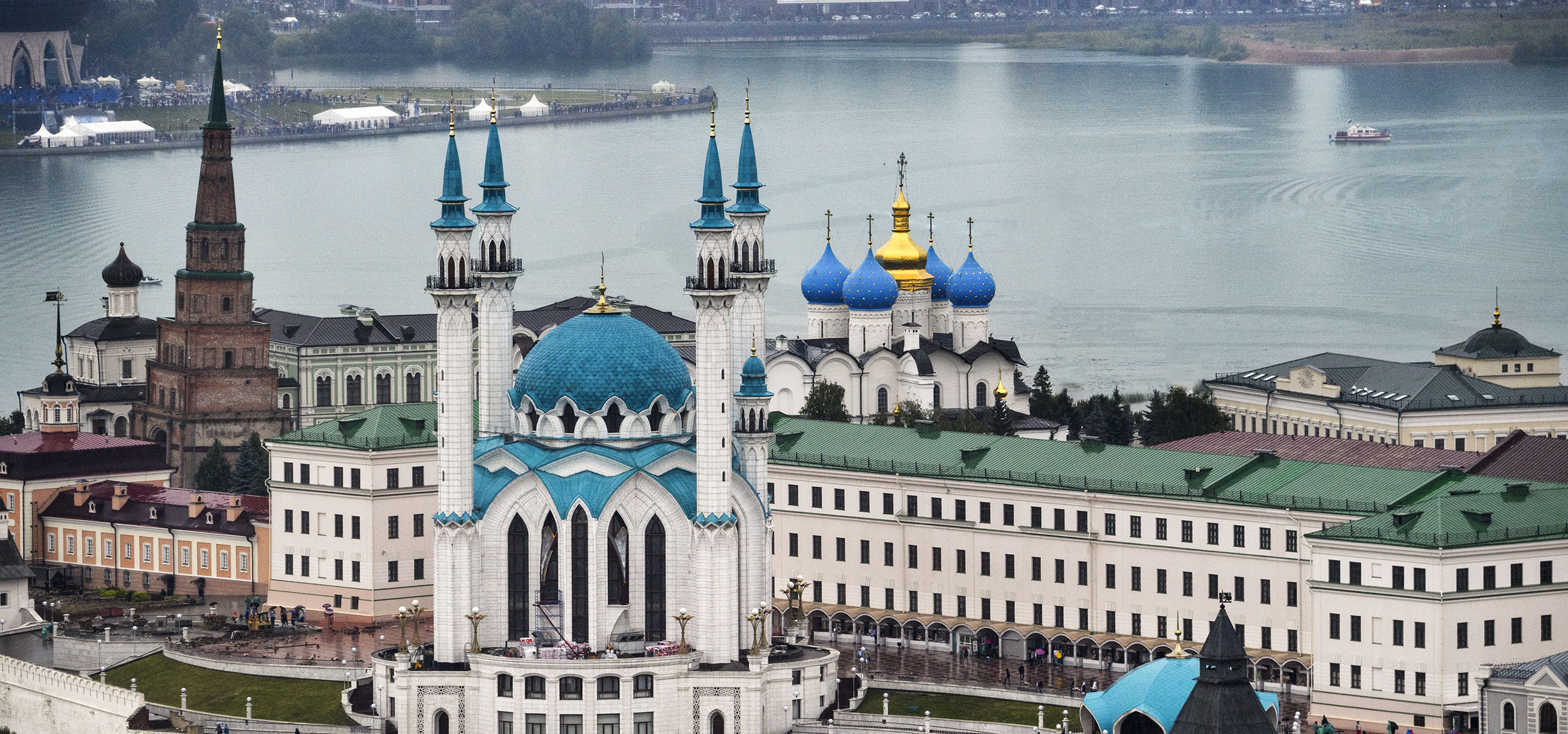 Teal spires of the Kazan Kremlin penetrate the sky with the confluence of the Volga and Kazanka rivers in the background in the city of Kazan, Russia.