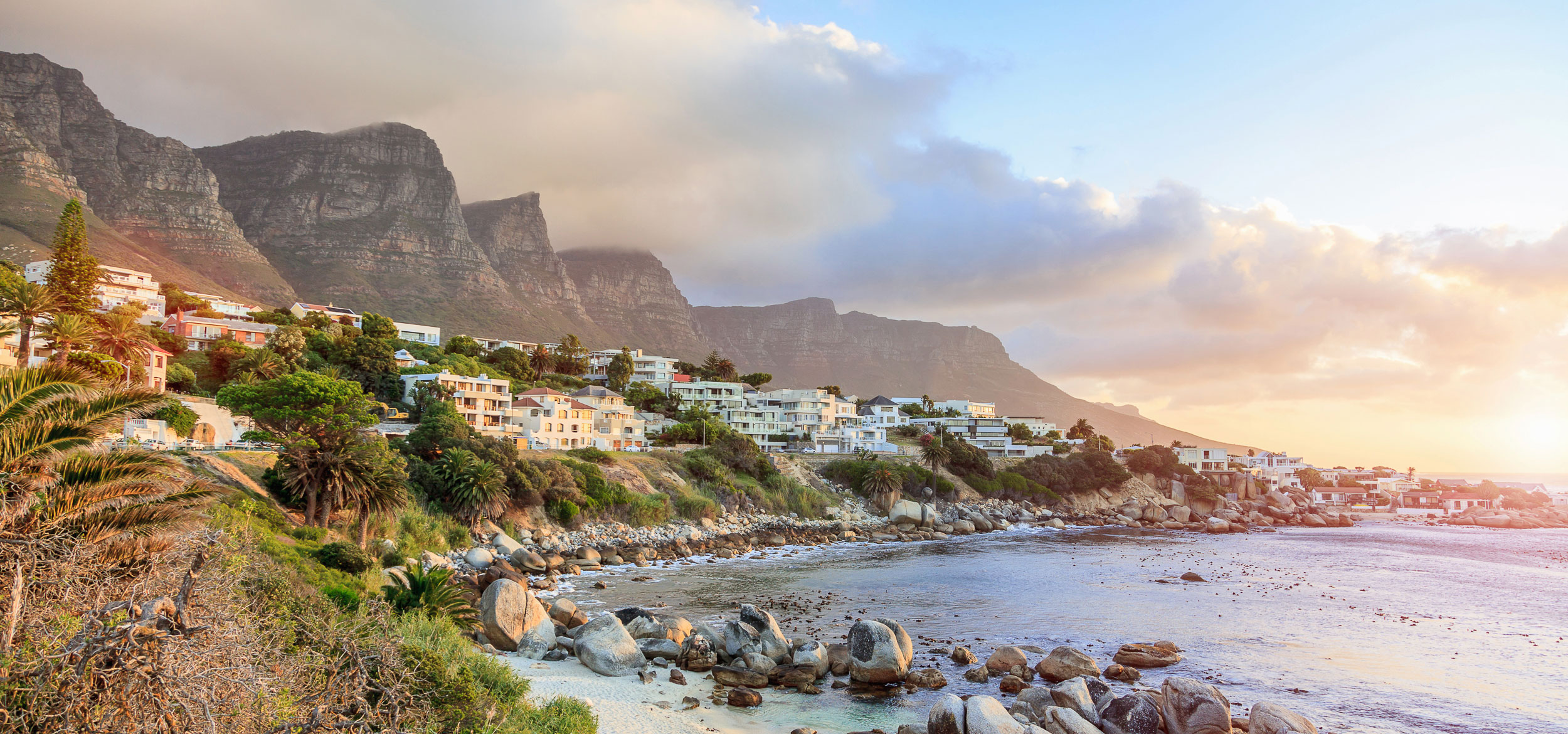 An aerial view of Cape Town Camps Bay with houses, ocean, and mountains in the background in Cape Town, South Africa.