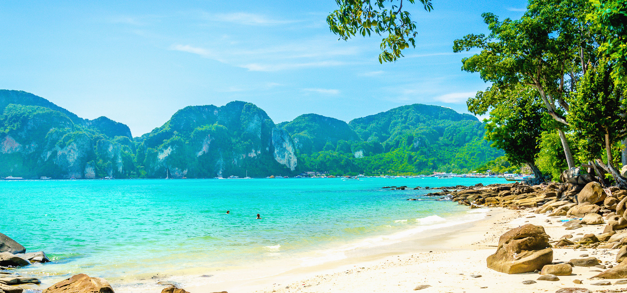 Verdant mountains make for a beautiful background to clear blue waters of a beach in Thailand.