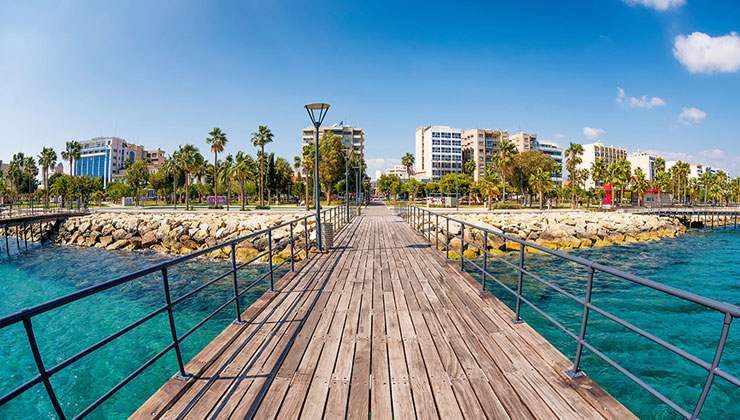View of old wooden pier over aqua colored water with town and palm trees in the background at the Enaerios Seafront in Limassol, Cyprus.