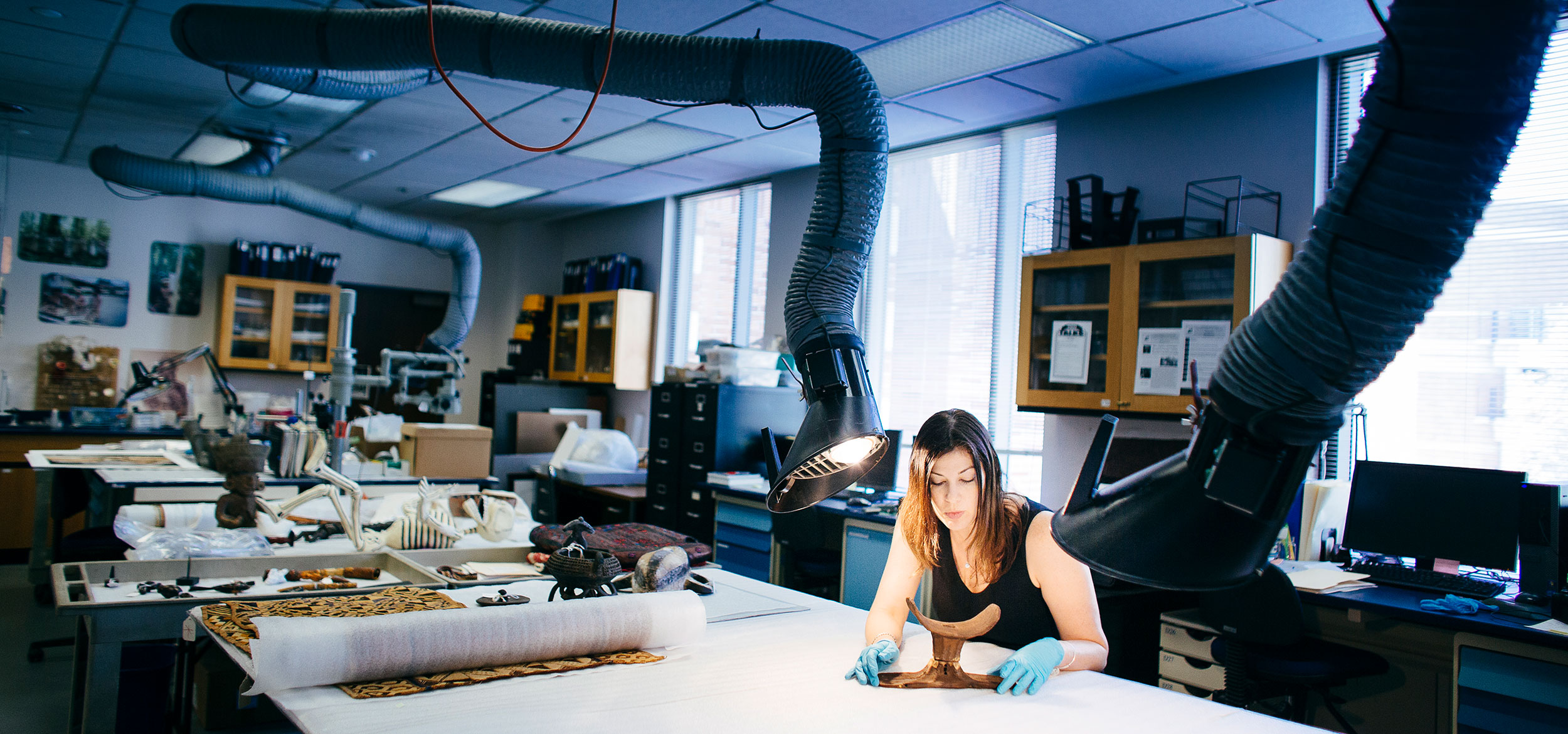 Female student analyzes artifact in lab.