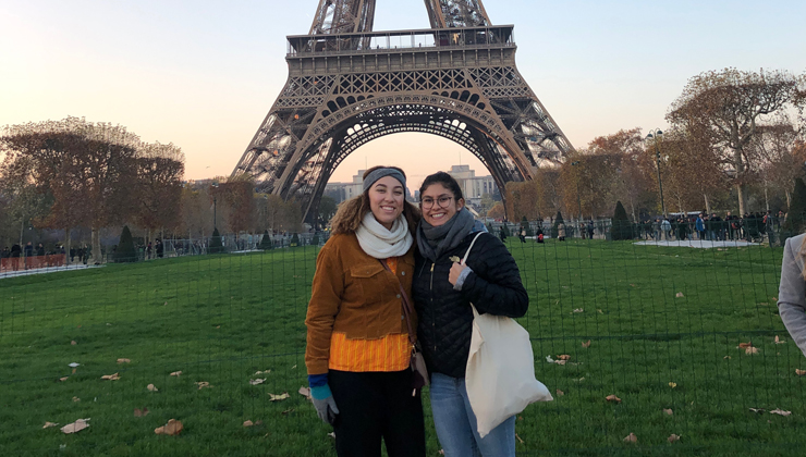 Two students standing in front of the Eiffel Tower in Paris France.