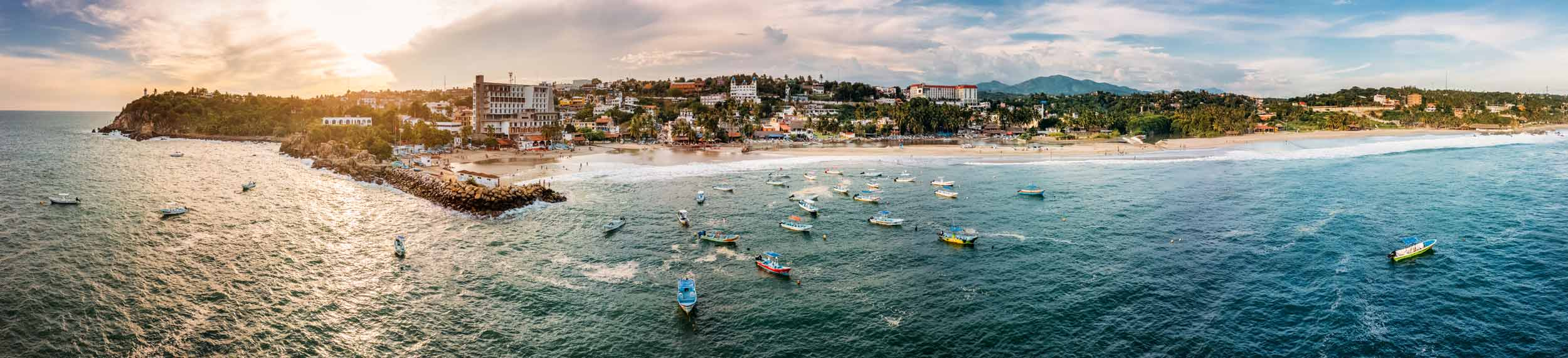 Aerial view of Puerto Escondido with colorful boats in the water, the port town, and beach access in Oaxaca, Mexico.