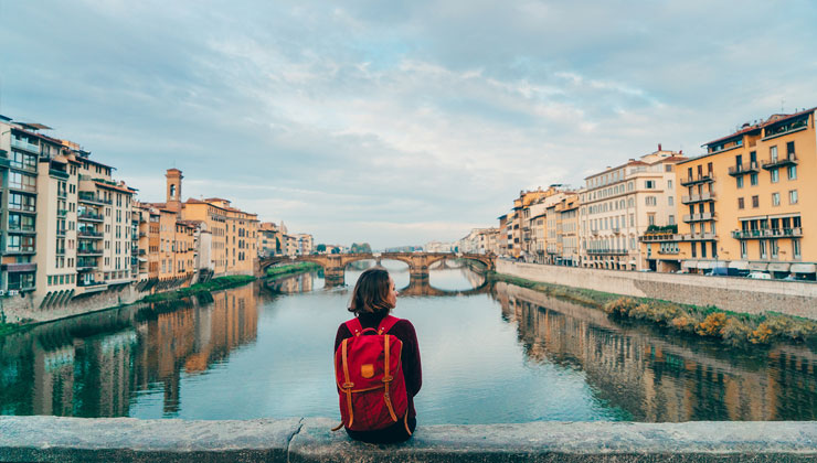 Student enjoys the view of Arno River and buildings from Ponte Veccio Bridge in Florence, Italy.