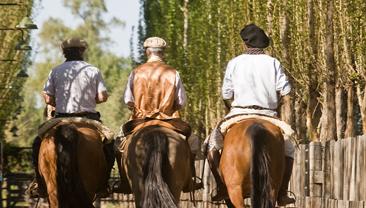 Three men on horses on a ranch.