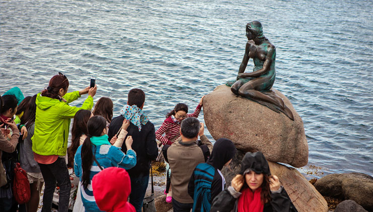 Tourists near the Little Mermaid Statue in Copenhagen, Denmark.