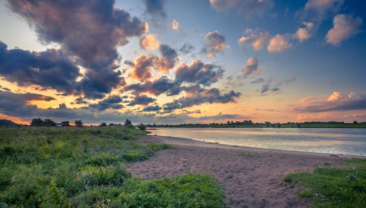 View of Wageningen Beach next to the Rhine River at sunset.
