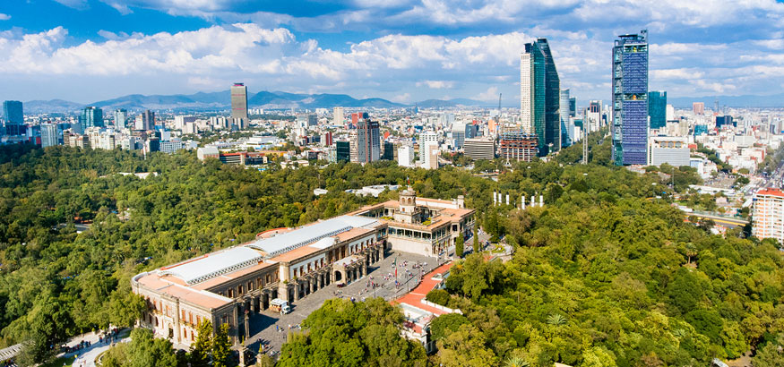 Aerial view of Mexico City skyline and lush green trees around Chapultepec Castle from Chapultepec Park in Mexico.