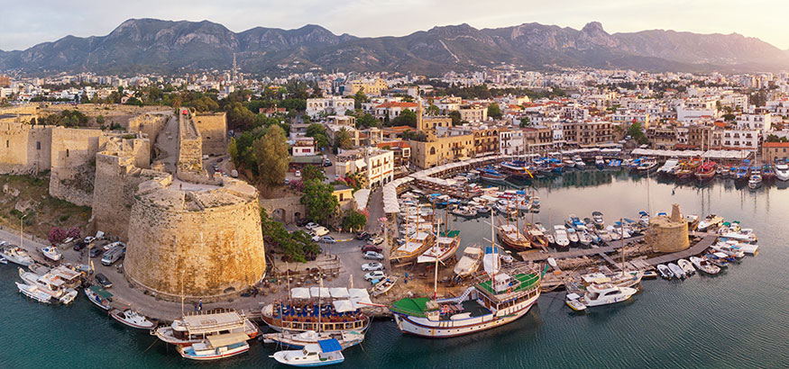 Aerial View of Old Marina in Girne (Kyrenia), Cyprus with mountains in background.