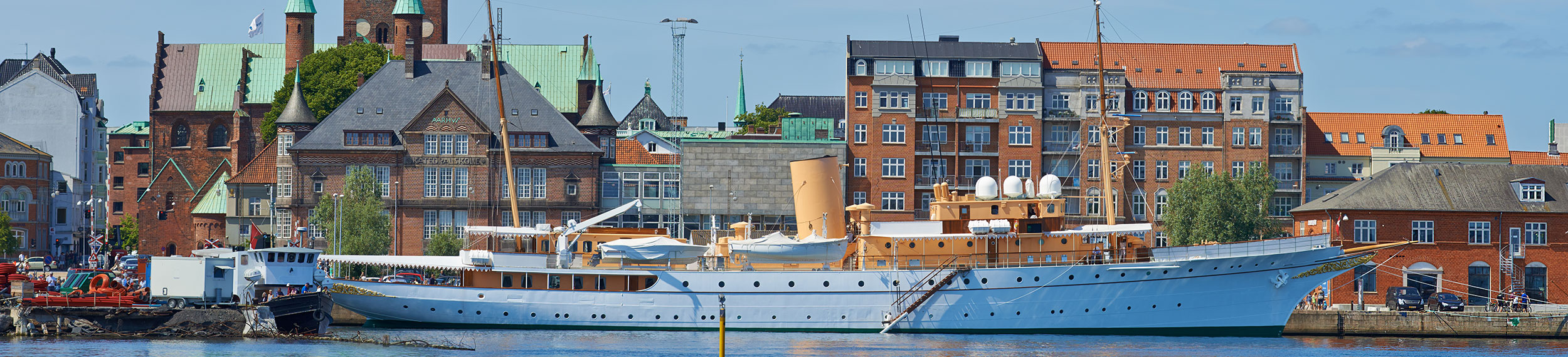 Her Royal Majesty's Yacht Dannebrog docked in the harbor on a beautiful day in Aarhus, Denmark.