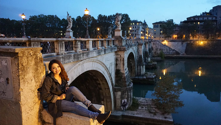 UC San Diego student on a ledge near a stone bridge a river at night in Rome, Italy.