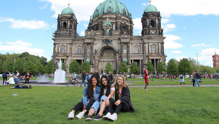 Three study abroad students sit on the green grass in front of the Berlin Cathedral on a beautiful day.