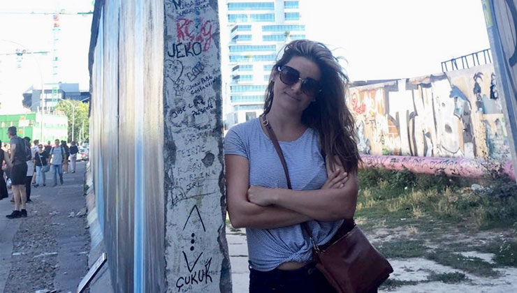 Study abroad student Laurina Sousa leans against a wall at the Eastside Gallery.