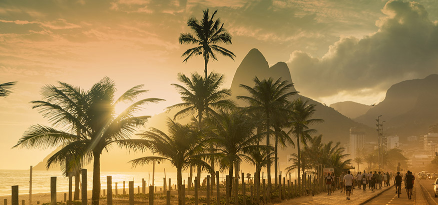 Pedestrians walking past a row of palm trees on Ipanema Beach at sunset in Rio de Janeiro, Brazil.