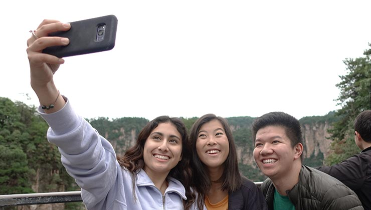 UC Irvine student Nicole Theresa Rodriguez takes a selfie with smiling friends in Zhangjiajie, China