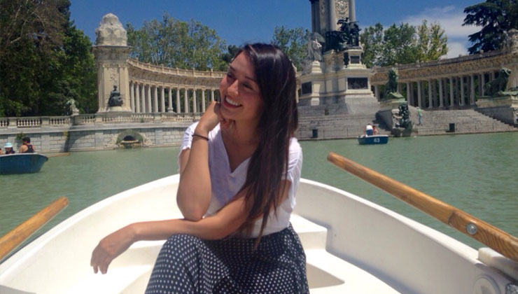 A student posing on a boat with a view of the Monument to Alfonso XII sculpture in Buen Retiro Park, Madrid.