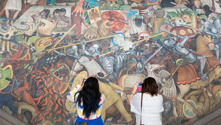 Two students take photos of the open-air mural near the steps of the National Palace in Mexico City, Mexico.