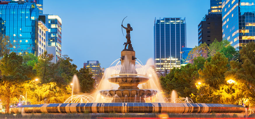 The Diana the Huntress Fountain on Paseo de la Reforma Avenue with a view of downtown Mexico City in the background.