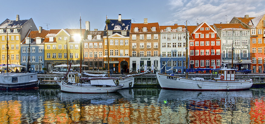 View of wooden ships and the colorful buildings of Nyhavn reflecting in the canal in Copenhagen, Denmark.