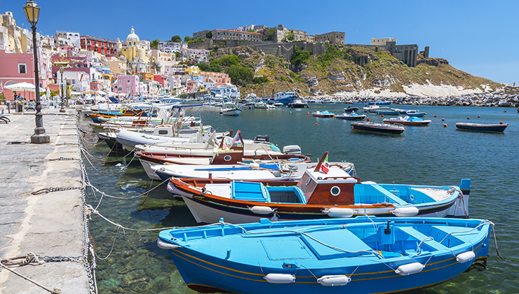 The port of Marina Corricella with colorful boats and houses in Terra Murata, Procida Island in Italy.