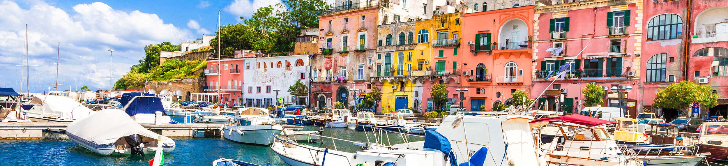 Blue and white boats sit in the aqua colored harbor with bright and colorful homes in Procida Island, Campania, Italy.