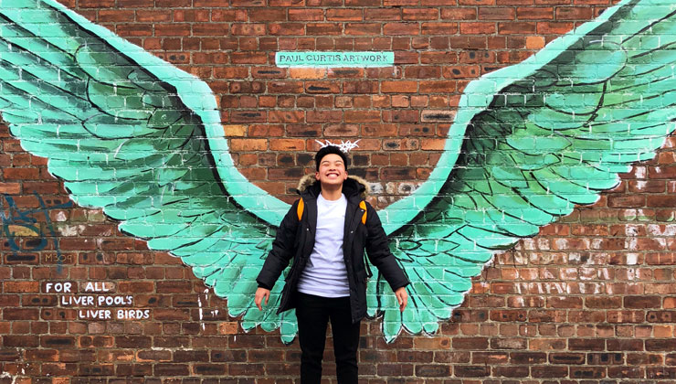 A student standing in front of mural of wings in Liverpool, England.