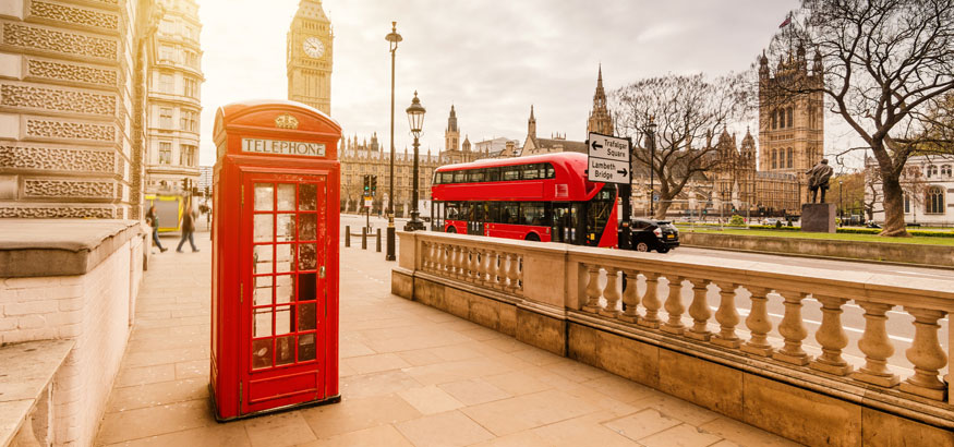 A red telephone booth with a double decker bus and Big Ben in the background in London England.