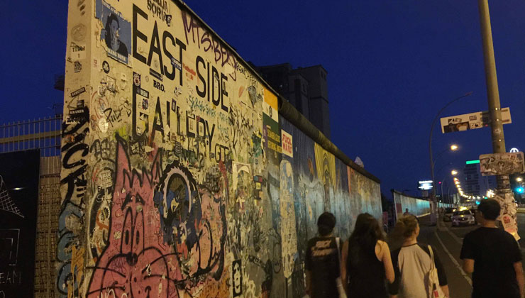 Group of students walk along the East Side Gallery in Berlin, Germany.