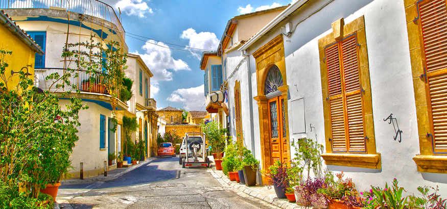 An alley of houses with colorful shutters under a blue sky in Nicosia, Cyprus.
