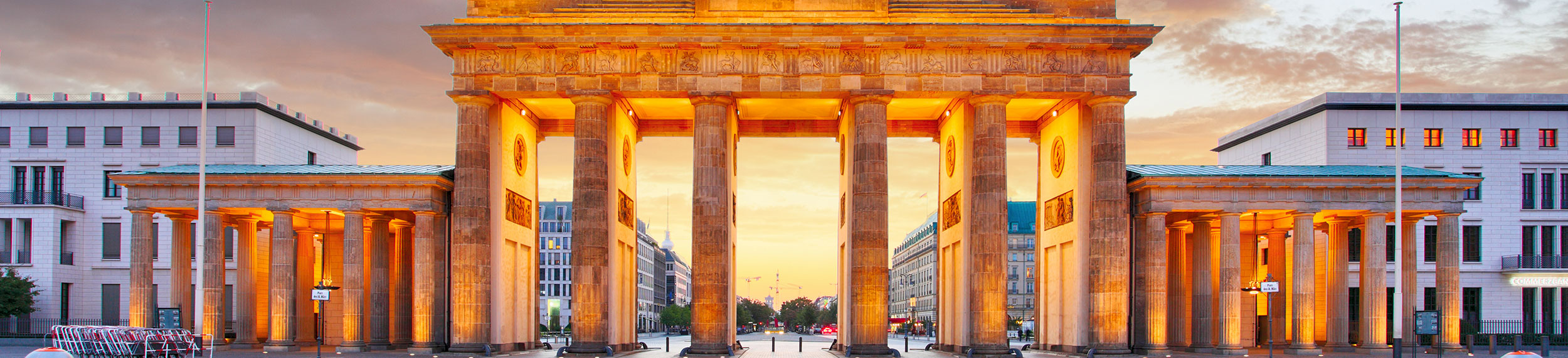 Brandenburg Gate lit up with an orange glow at dusk in Berlin, Germany.