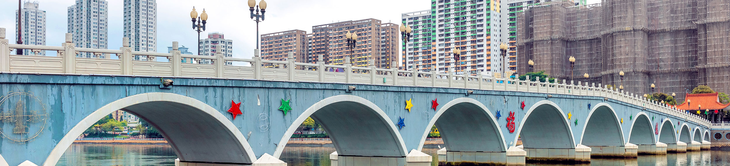 Colorful bridge with residential district of Sha Tin, Hong Kong in the background.