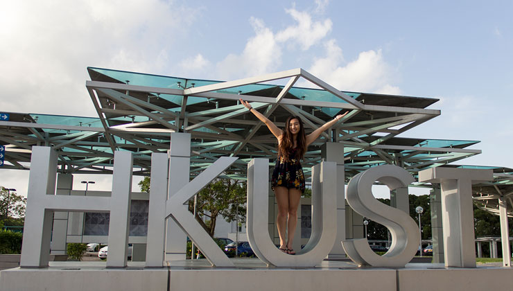 Student stands in the U of the HKUST artwork at the Hong Kong University of Science and Technology.