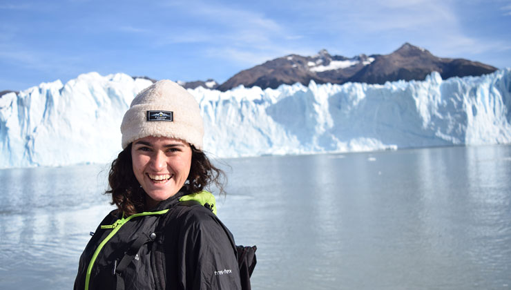 Brenna Cancilla of UC Berkeley smiles in front of an almost frozen lake and glacier at Glaciar Perito Moreno in Argentina.