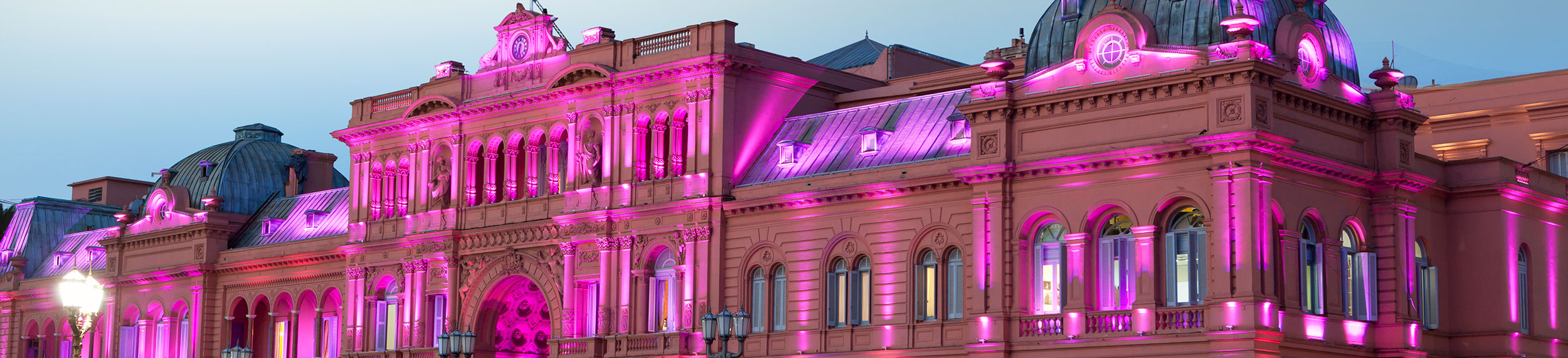 Casa Rosada in Buenos Aires, Argentina is lit up in a pink hue in the evening with a blue sky and wispy clouds above.