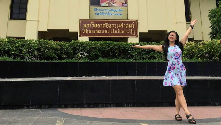A student posing with her arms in the air at Thammasat University in Bangkok, Thailand.