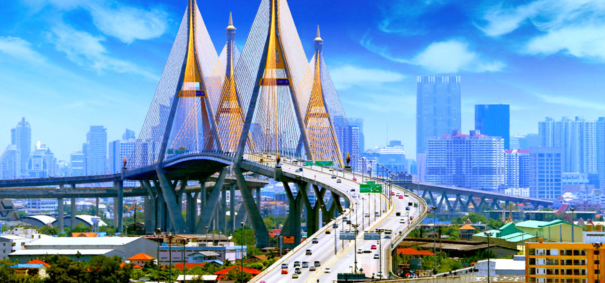 Bhumibol Bridge with traffic and blue buildings in the background in Bangkok, Thailand.