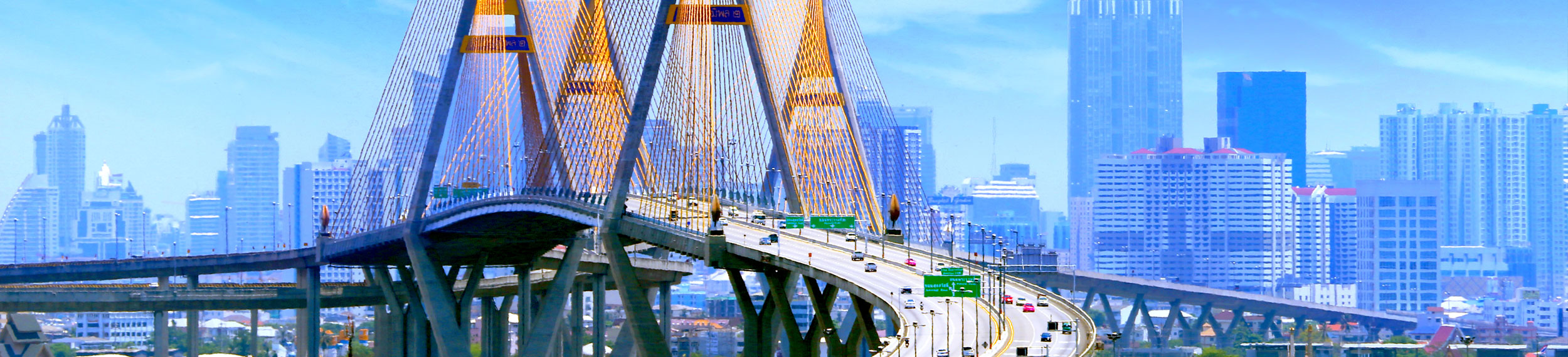 international-Bhumibol Bridge with traffic and blue buildings in the background in Bangkok, Thailand.